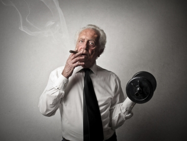 senior businessman smokes a cigar and does exercise